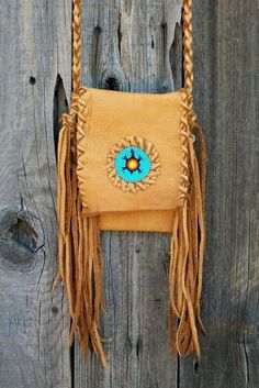 """This fringed leather purse is the perfect bag when you want to travel light. This crossbody shoulder bag features tied fringe down the sides and a beaded turtle totem for the person who wants to be different. The shoulder strap is a four point braided strap which can be thrown over your shoulder or go across the body. I have even tied mine around my waist for a hip bag. It's great for your android phone, glasses. keys or whatever your needs may be.  This bag measures 6 """" tall x 5 1/2"""" ..."""
