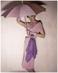 Model holding pink parasol wearing Traina-Norell's pink belted, button top rayon and wool,1944 Photo John Rawlings