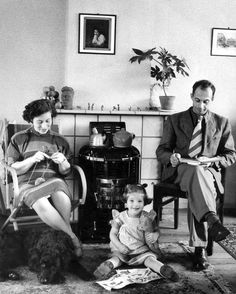 Gezin bij de potkachel met daarop twee ketels, jaren '50. Moeder breit, vader leest boek, -dochtertje en hond aan de voeten. Aan de muur: reproductie van Rembrandts 'Meisje leunend uit een venster'. 1954.