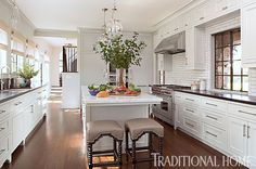 The renovated white kitchen features a central island. - Photo: Karyn Millet / Design: Joe Lucas and Parrish Chilcoat