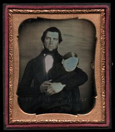 Father holding dead child in post mortem photo.