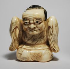 An ivory netsuke of a kneeling karako masquerading as a Noh performer with a very expressive 'Buaku' mask over his face. The diaphanous folds of his kimono are realistically rendered with finely engraved details of butterflies and kiku blossoms. Signed Meikosai Hoichi.  Ex. Meinertzhagen Collection. Ills. MCI, page 167. Mid 19th Century.  Height: 3.7 cm