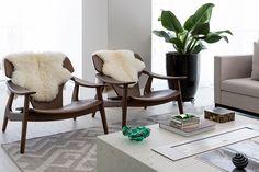 Sala de estar com poltronas de madeira, sofá branco e mesa de centro branca.