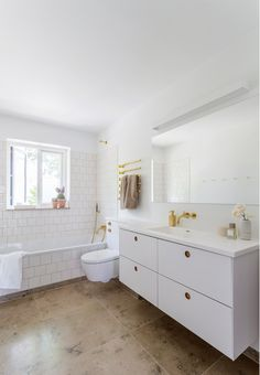 Modern bathroom with beautiful brass faucets and different tiles.