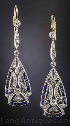 Art Deco Diamond and Sapphire Drop Earrings. These long and sexy Art Deco dazzlers, delicately hand crafted in platinum over 18K gold, measure over 1 1nd 1/2 inches and glitter with an array of European and rose-cut diamonds dramatically accented with royal blue calibre-cut sapphires. The classic tear drop shape bottoms are pierced with a decorative geometric design and swing and sway below slender tripartite tops for a striking and stunning effect.