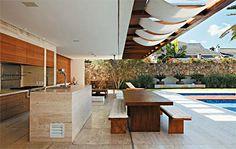 Madeira, vidro e pedra marcam esta casa voltada para a área de lazer