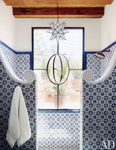The curves at the top of the walls, the Moroccan star pendant, the center pivoting round window, and of course, the tile, give me shower envy (and I just remodeled our master bath!).  [blue tile shower architectural digest]