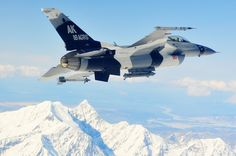 An F-16 Falcon in OpFor colors soars over the Alaska Range on 20 April 2010.