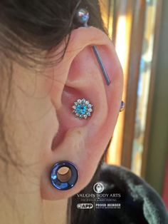 Stunning stunning conch piercing featuring a Rose from BVLA.   14k white gold, genuine Ice Blue diamonds and VS White diamonds on the outside, and a stunning Paraiba Topaz in the center.   vaughnbodyarts Monterey, CA