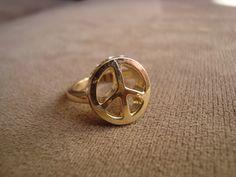 """Anel em metal dourado com o símbolo de """"Paz e Amor"""" e aplicação de strass Swarovski branco.  Disponível nos aros 15 (diâmetro: 1,7cm) e 19 (diâmetro: 1,8cm). Favor especificar o tamanho no espaço para comentários/observações durante o check out. R$33,00"""