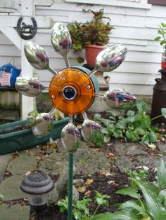 This is a garden flower made from old spoons and a round reflector.. Barn Al's back yard decor....