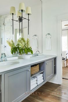 ASHLEY GILBREATH INTERIOR DESIGN: A large mirror behind the grey double vanity reflects daylight in this Rosemary Beach master bathroom. Built-in shelves provide storage for towels. A Visual Comfort double sconce in bronze gives the space a sophisticated edge. Small Dining, Dining Area, Kitchen Dining, Ashley Gilbreath, Beautiful Beach Houses, Boy Bath, Rosemary Beach, Bunk Rooms, Coastal Bathrooms