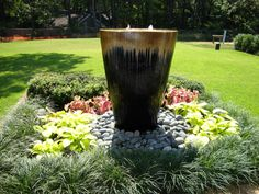 Easy focal-point, large glazed pot with pebble surround then symetrical plantings using colour palette Chartreuse and Burgundy bordered with mondo grass.