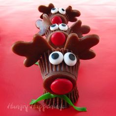 """Resee's Cup Rudolph the Red Nose Reindeer Treats for Christmas....use Resee's Peanut Butter cups, chocolate icing for the """"glue"""" red M&M for the nose, strip a green Fruit Roll Up for the scarf and candy eyes (or dip M&M in white chocolate and dab some chocolate icing on it to make the eyes) the antlers are softened dark caramels!!!! TOO CUTE!"""
