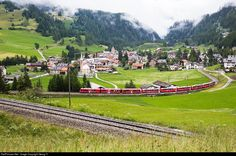 """The BERNINA EXPRESS, running from Chur via Albula and Bernina to Tirano/Italy, pulled by highpower """"Allegra"""" railcar ABe 8/12 # 3506 with name """"Anna von Planta"""", on the lowest level of the reversing loops above Bergün. In one and a half minute the train will run from the left, on the track of the second level in the foreground, towards Preda."""