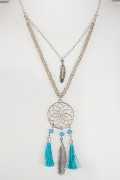 This silver necklace features two chains. The first has a feather charm, and the second has a dream catcher, complete with tassels and a feather.