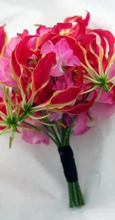 Gloriosa lilies... and sweet peas.... best combo ever <3 except I would like cascading down with ferns.... - EJ