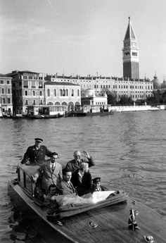 Ernest Hemingway (waving), Mary Hemingway, and unidentified others on a canal boat/taxi on the Grand Canal in Venice, Italy.  The Campanile di San Marco (bell tower) is in the background. [via JFK Presidential Library & Museum]