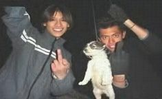 Two men hanging a puppy with string with shown an obscene gesture with their fingers