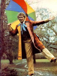 Le sixieme doctor porter un manteau, un pantalon, une chemise, et un cravate. Le manteau est orange, jaune, et rouge. Le pantalon est jaune. Les cravates sont bleu, est sont tres interessent. Le costume est bizarre.