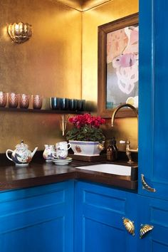 Small blue and gold kitchen in a small flat with antique furniture & patterned wallpaper. Interior design ideas and inspiration for small spaces on HOUSE by House & Garden.