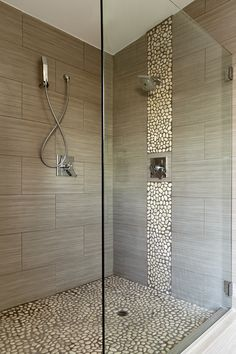 Pebble mosaics add an earthy vibe to this walk-in shower. | Floor & Decor
