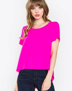 – Hot pink short sleeve top – Asymmetrical hem in the back – Woven  Size + Fit – Model is wearing size S – Measurements taken from size S – Length: 26
