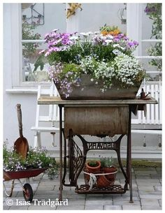 Old trundle sewing machine stand used as a flower planter holder. And did you notice the tiny wheelbarrow? Sweet!