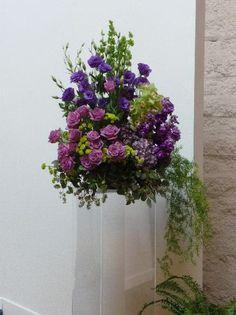 #weddingflowers #weddingceremony #ceremonyflowers #purple #greenery #acrylicpedestal #pedestalarrangement