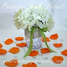 White hydrangea centerpiece with orange rose petals & diamond confetti.