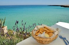 Eating taralli (a local snack) while overlooking the water at Lido Bianco in Monopoli, Puglia. One of the best summer meals, and escapes, in Italy.