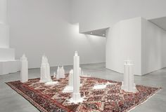 """Babak Golkar:Grounds For Standing and Understanding, 2012  Grounds for Standing and Understanding, is an installation that utilizes the design elements and intricate patterns of a Persian carpet as a foundation to literally """"draw up"""" and transform into three-dimensional scale models that resemble architectural mega-towers. These sculptural forms recall some early modernist architectural styles such as Brutalism, Russian Constructivism and Art Deco, as well as, referencing buildings ..."""