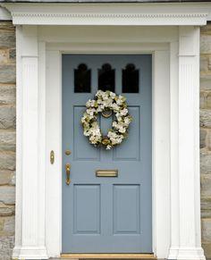 The front door has a brass lock, door handle, mail slot, and door knocker, a white door casing with a brass plated doorbell.