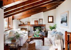 Salón rústico con techo de madera, chimenea de piedra y dos sofás enfrentados