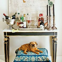 An adorable puppy points guests toward a well-stocked bar cart.