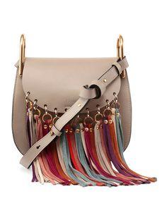 Chloe small shoulder bag in smooth calfskin leather. Brass hardware with pale golden trim. Adjustable shoulder strap. Flap top with snap closure. Multicolor suede fringe at front. Interior pocket. App