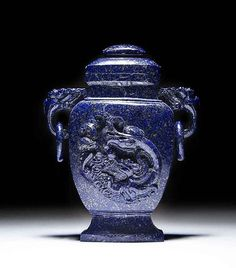 CHINESE CARVED LAPIS VASE AND COVER, with elephant head and ring handles and carved with a dragon, of baluster shape with a flared foot.