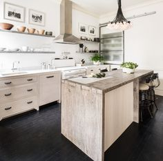 Treat your eyes to this beautiful kitchen decorated with a reclaimed wood island and a rustic pendant light fixture.