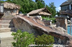 Hand Carved Concrete waterfall and tiled waterslide on a back yard swimming pool.
