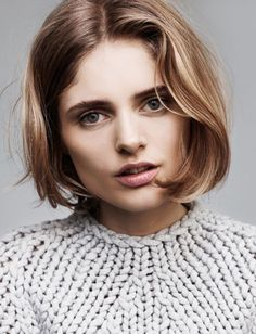mischa barton with dark blond, wavy middle parted bob haircut, wearing light grey, cable knit sweater