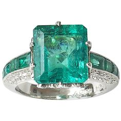 Moira Emerald Diamond platinum Ring -- A Moira emerald ring with a central, emerald-cut emerald weighing approximately 7.10ct, with four, graduating, emerald-cut emeralds in the shoulders, in millegrain edged channel settings. The decorative bezel and sides of the shoulders are pavé set with old-cut diamonds, mounted in platinum.