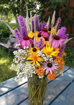 Coneflowers are like a whimsicalcross between daisies and sunflowers. They work well with just about any summer flower, so they're a great addition if you're looking for variety. They're the deep pink flowers in the picture below. Put them in your bouquet orstone and copper vase. | Coneflowers | 7 Must Have Summer Wedding Flowers | My Wedding Favors