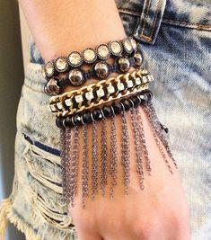 Kit de pulseiras femininas, composto de 4 pulseiras sendo: <br>- 1 pulseira shambala com cristais pretos e franjas de corrente em banho grafite <br>- 1 pulseira de corrente dourada, entrelaçada com corrente de strass e camurça preta <br>- 1 pulseira shambala de pérolas grafite <br>- 1 pulseira de metal com detalhes em strass light peach e banho prata antiga. <br> <br>> informe no pedido o tamanho do seu pulso que faremos personalizada para melhor ajuste. Para medir seu punho, use uma linha…