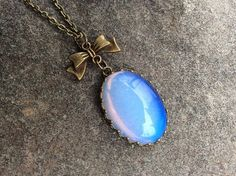 This Listing is for a Antique Bronze, milky blue Glass Opal necklace in a oval crown  Setting.
