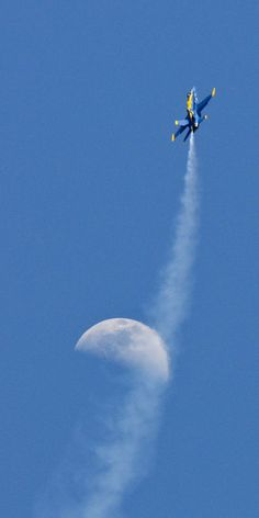 Jet from the Blue Angels performs during air show, with the moon in the background.