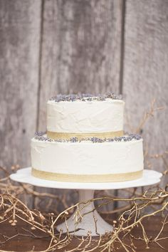 lavender topped wedding cake with gold ribbon