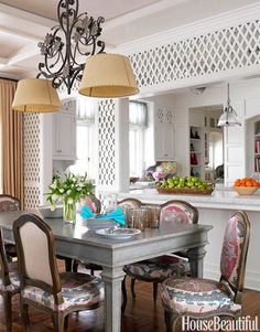 To balance the diamond pattern on the walls, Allison Caccoma used softer lines and curves in this breakfast room's chandelier and chairs. The floral colors of the  fabric, a Robert Kime suzani, provides a burst of color against the all-white kitchen and helps the space feel like an extension of the garden. John Valiant  - HouseBeautiful.com