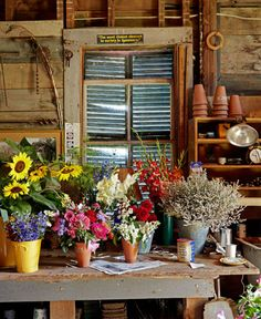 The owner of this New Hampshire home uses a worktable as a space to arrange cut-flower bouquets from his gardens.   - CountryLiving.com