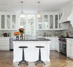 A stainless steel French kitchen hood, illuminated by Boston Functional Library Wall Lights, stand in front of windows and over a Wolf dual range. French Kitchen, Custom Kitchen, Herringbone Wood Floor, Kitchen Window, Eclectic Kitchen, Home Decor, Kitchen, Herringbone Floor, Kitchen Hoods