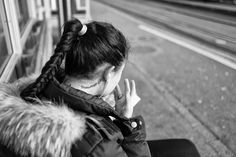 Girl with a tatoo on her neck, sitting at a tram stop in Zurich fixing her make up. Street Pictures, Zurich, Typo